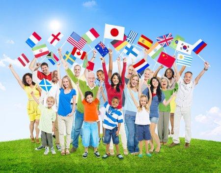 Photo pour Multiethnique personnes tenant des drapeaux nationaux du monde - image libre de droit