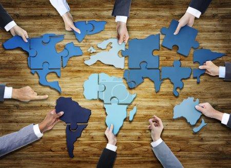 Photo pour Groupe de gens d'affaires avec Jigsaw Puzzle formant dans la carte du monde - image libre de droit