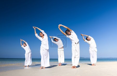 People performing yoga on beach