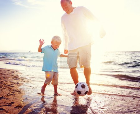 Father and Son Playing with ball on the beach