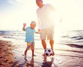 Otec a syn hraje s míčem na pláži