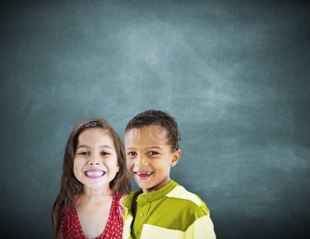 Children smiling at blackboard