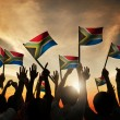 Group of People Waving South African Flags in Back...