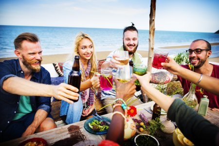 cheerful friends hanging out on the beach party