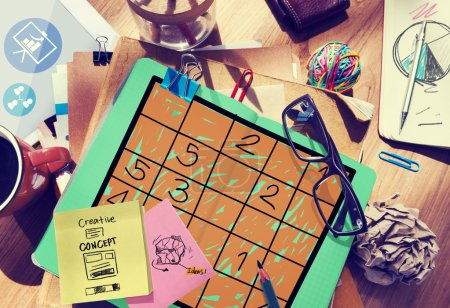 Messy office desk with Sudoku