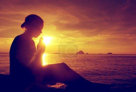 Young woman praying at sunset