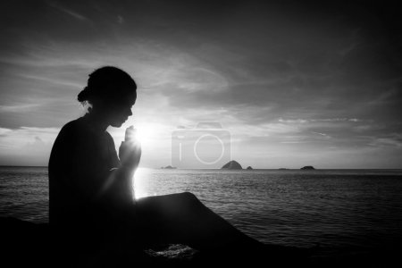 Young woman praying at sunset
