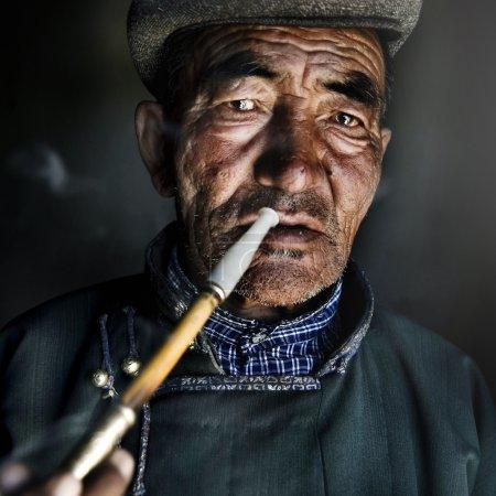 Mongolian Man Smoking a Pipe