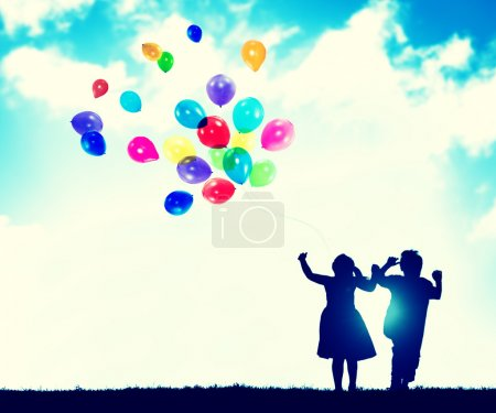 Children playing together with balloons