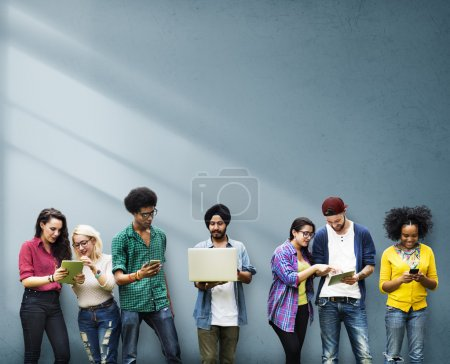 Photo for Young cheerful diverse college students using wireless devices - Royalty Free Image