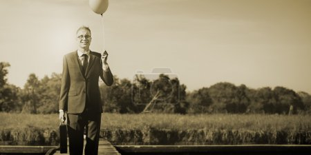 Businessman with balloon at outdoors