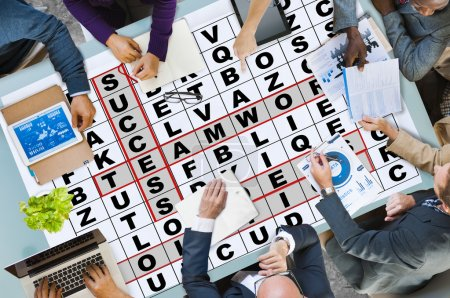 Business People Pointing on Crossword