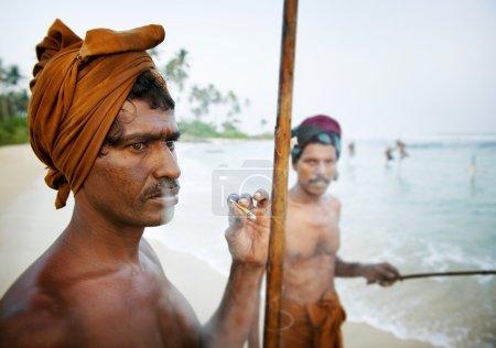 Fisherman smoking by shore