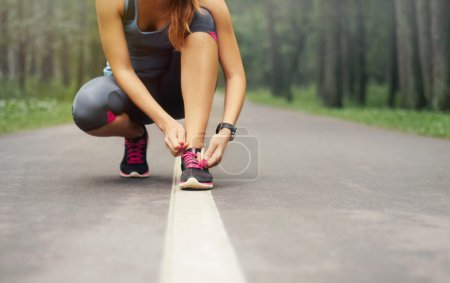 Photo for Young sporty woman preparing to run in early foggy morning in the beautiful nature forest, wellness concept - Royalty Free Image