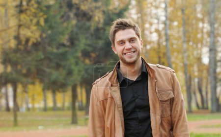 Portrait of attractive happy smiling stylish young man in autumn park, outdoors background
