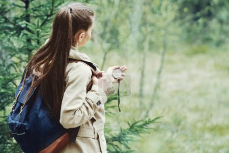 young woman discovering nature in the forest with compass in han