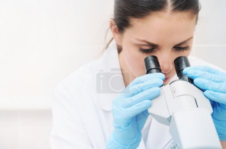 close up portrait of young medical researcher looking through mi