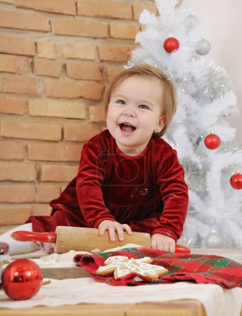 happy little baby girl with big blue eyes in red dress making co