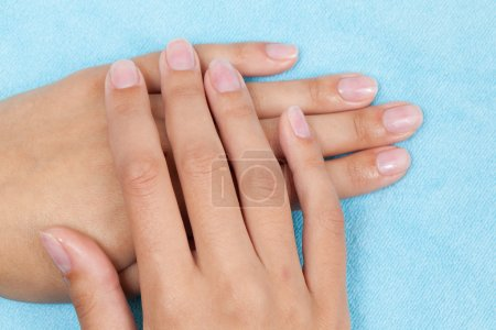 Woman hands on light blue background