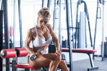 Sportive woman doing exercise with dumbbells