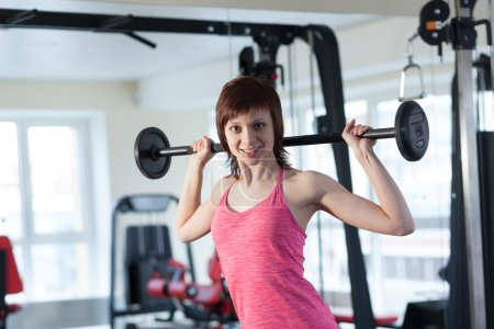 Photo for Smiling woman doing exercise with a barbell in the gym - Royalty Free Image