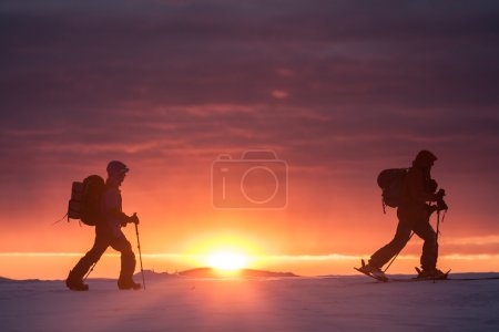 Two skiers walking on the mountain against sunset...
