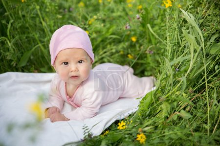 Baby girl crawling on the grass