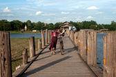 Vesničané cyklopřívěsů o most U Bein, Myanmar