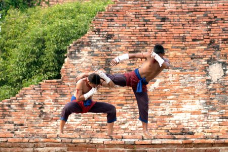 Photo for AYUTTHAYA,THAILAND-MAR 26,2010 : Warriors frighting Thai boxing during Wai Kru Muay thai Ceremony and Muay Thai Festival at The Wat Phutthaisawan in Ayutthaya old city, Thailand. - Royalty Free Image