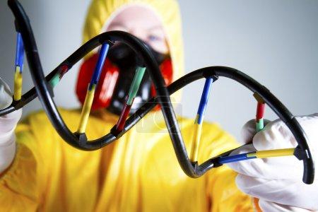 Photo pour Femme habillée en costume HazMat avec masque à gaz et bouclier à double hélice - image libre de droit