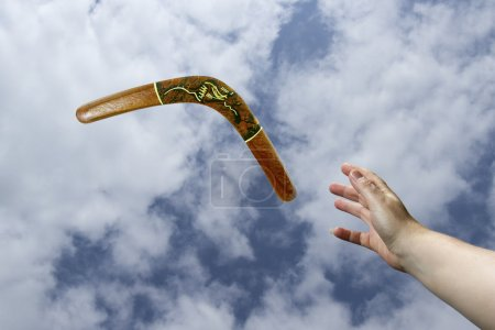 Photo for Hand catching a painted, wooden boomerang midair with blue sky and cloud background. - Royalty Free Image