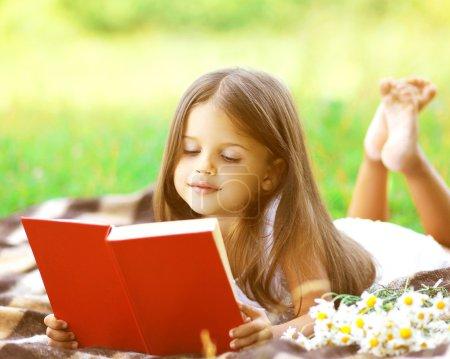 Photo pour Enfant lisant un livre sur l'herbe - image libre de droit