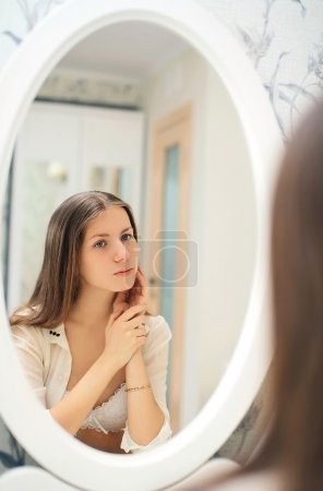 Cute young girl looks at herself in the mirror