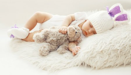 Baby comfort! Sweet infant at home sleeping with teddy bear on t