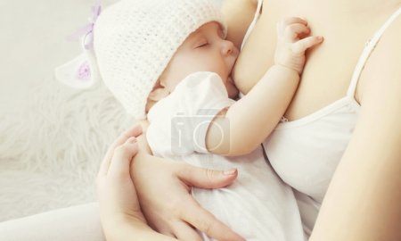 Soft photo mother feeding breast her baby at home