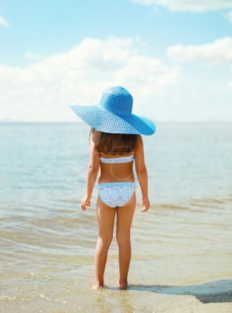 Summer travel photo pretty little girl in straw hat on the beach