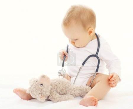 Baby playing and listens stethoscope teddy bear