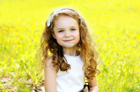 Portrait of cute little girl child outdoors in sunny summer day