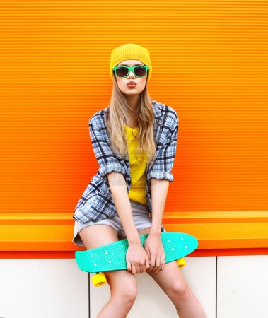 Photo for Fashion hipster cool girl in sunglasses and colorful clothes with skateboard having fun against the orange wall - Royalty Free Image