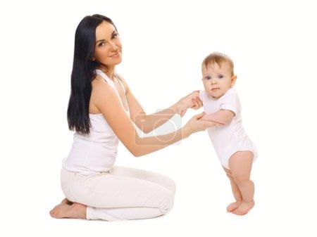 Photo pour Mère aide l'enfant à faire les premiers pas - image libre de droit