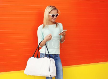 Photo for Fashion portrait of pretty smiling woman in sunglasses with bag using smartphone against the colorful orange wall - Royalty Free Image