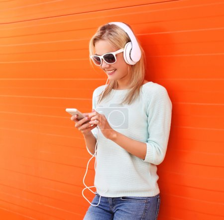 Photo for Fashion, technology and people concept - pretty smiling girl listen to music in headphones and using smartphone against the colorful orange wall - Royalty Free Image