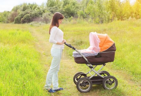 Happy young mother walking with baby stroller outdoors on the na