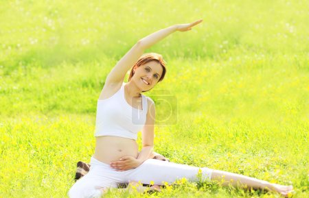 Pregnant woman sitting on the grass doing fitness or yoga exerci