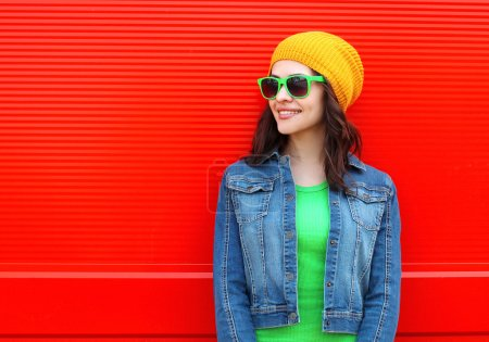 Photo for Fashion portrait of pretty young smiling woman wearing a sunglasses and colorful clothes against the red background - Royalty Free Image
