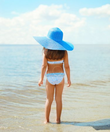 Back view of beautiful little girl child in swimsuit and straw h