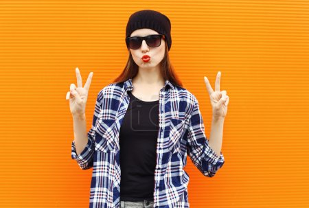 Photo for Fashion portrait pretty cool girl wearing a black hat, sunglasses and shirt over colorful background - Royalty Free Image