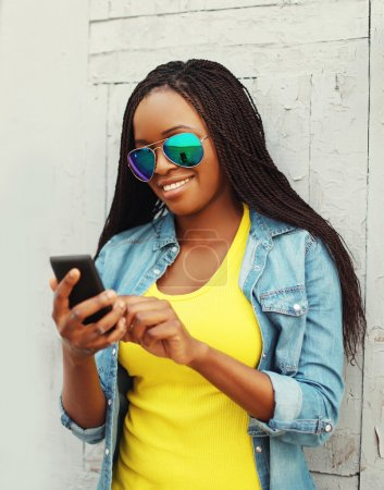 Beautiful smiling african woman using smartphone in city