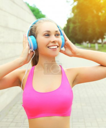Portrait fitness happy smiling woman with headphon...