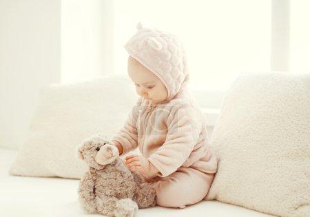 Photo pour Bébé mignon jouant avec un jouet ours en peluche à la maison en chambre blanche - image libre de droit